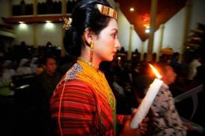 A Toraja's girl in traditional attaire with a holy mass candle.