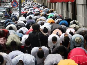 Italian Muslims performing Friday prayer in a pavement of Milan , Italy.