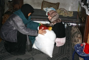 Sister Khadijah, one of the volunteers of Sahabat Al Aqsha of Indonesia, delivering food aid to an elderly widow whose legs are paralyzed from being tortured for three consecutive months in prison, in one of the villages in Aleppo, Syria, amid the uproar of bomb attacks. Photo: Sahabat Al-Aqsha