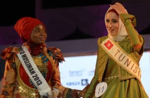 Winner of the 2014 World Muslimah Awards Fatma Ben Guefrache (R) of Tunis reacts and touchs her crown as Miss Muslimah 2013 Obabiyi Aishah Ajibola (L) of Nigeria looks on during the grand final in Prambanan, Yogyakarta. Photo: AFP